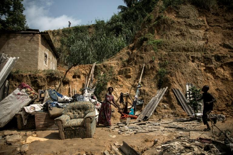 A child walks past (R) and a woman stands among the remains of a landslide in Ngaliema district on January 5, 2018 in Kinshasa. Thirty-seven people died overnight when torrential rain and mudslides swept though shanty homes in Kinshasa