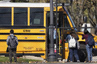 FILE - In this Friday, Nov. 6, 2020 file photo, students wait to board a school bus in Wheeling, Ill. With COVID-19 infections and hospitalizations spiking to record numbers across the U.S. and abroad, many school districts are temporarily shutting down in-person classes as holidays loom. (AP Photo/Nam Y. Huh)