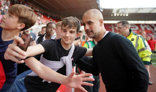 "Soccer Football - Premier League - Southampton vs Manchester City - St Mary's Stadium, Southampton, Britain - May 13, 2018 Manchester City manager Pep Guardiola poses for a photograph with a fan after the match REUTERS/David Klein EDITORIAL USE ONLY. No use with unauthorized audio, video, data, fixture lists, club/league logos or ""live"" services. Online in-match use limited to 75 images, no video emulation. No use in betting, games or single club/league/player publications. Please contact your account representative for further details."