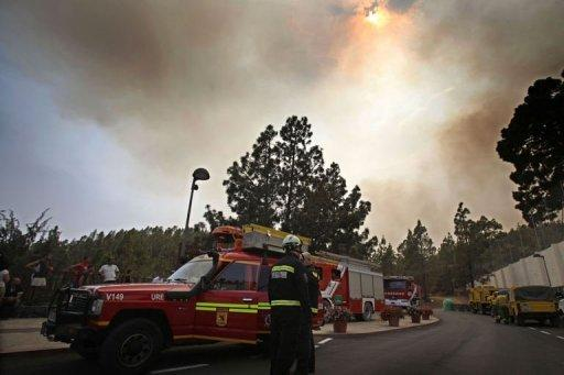 "Firemen stand next to their truck in the town of Vilaflor on the Spanish Canary Island of Tenerife. Emergency services ""are evacuating residents from Vilaflor due to the advance of the fire from the east,"" the regional government said"