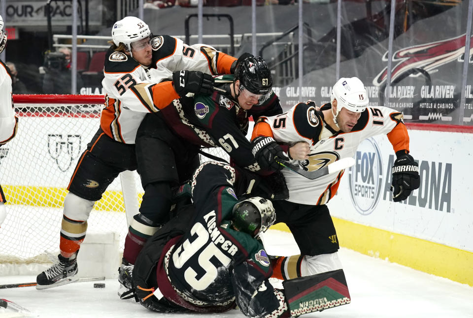 Anaheim Ducks left wing Max Comtois (53) and center Ryan Getzlaf (15) fight with Arizona Coyotes left wing Lawson Crouse (67) and goaltender Darcy Kuemper (35) in the first period during an NHL hockey game, Monday, Feb. 22, 2021, in Glendale, Ariz. (AP Photo/Rick Scuteri)
