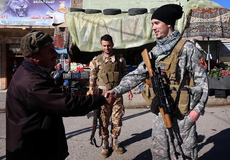 """US national """"Brett"""" (R) shakes hands with a passer-by in the town of Al-Qosh, in northern Iraq, where he is fighting Islamic State (IS) jihadists alongside Christian militia group Dwekh Nawsha (AFP Photo/Safin Hamed)"""