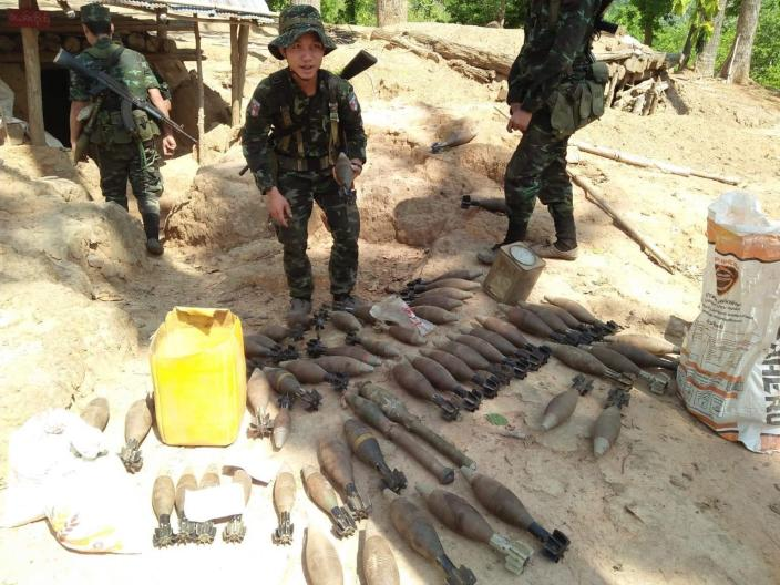 In this photo provided by Karen National Liberation Army, a Karen National Liberation Army soldier holds a motor shell while standing next to a cache of mortar shells found at a Myanmar military outpost Friday, May 7, 2021, in Mutraw district, Karen State, Myanmar. Ethnic Karen guerrillas burned down a Myanmar military outpost Friday morning, capturing it without a fight after its garrison fled at their approach, a senior Karen officer said. (Karen National Liberation Army via AP)