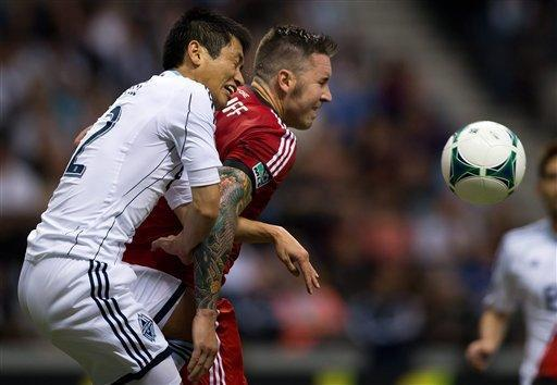 Vancouver Whitecaps' Lee Young-Pyo, left, of South Korea, and Toronto FC's Danny Califf vie for the ball during the second half of an MLS soccer game in Vancouver, British, Columbia, Saturday, March 2, 2013. (AP Photo/The Canadian Press, Darryl Dyck)