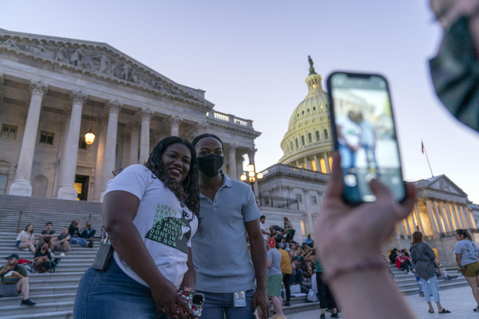 Rep. Cori Bush, D-Mo., take a picture with a supporter as she camps outside the U.S. Capitol, in Washington, Monday, Aug. 2, 2021, as anger and frustration has mounted in Congress after a nationwide eviction moratorium expired at midnight Saturday. (AP Photo/Jose Luis Magana)