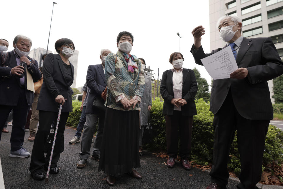"""Plaintiffs and their supporters gather to walk toward the Tokyo District Court Thursday, Oct. 14, 2021, in Tokyo. The court is hearing five ethnic Korean residents of Japan and a Japanese national demanding the North Korean government pay compensation over their human rights abuses in that country after joining a resettlement program there that promised a """"paradise on Earth,"""" but without the presence of a defendant - the North's leader. (AP Photo/Eugene Hoshiko)"""