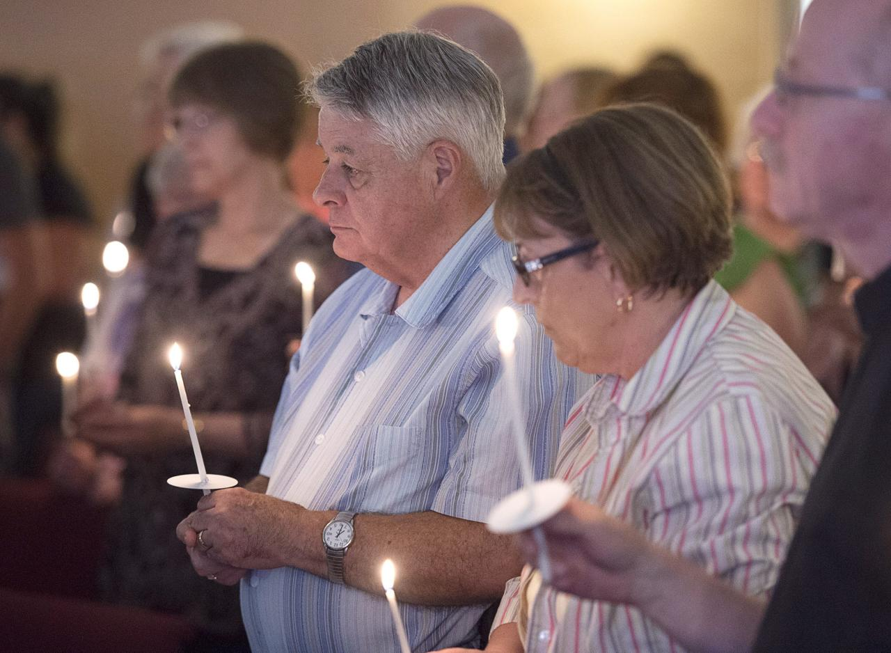 <p>Residents attend a candlelight vigil at St. John the Evangelist Anglican Church in Fredericton on Friday, Aug. 10, 2018. Two city police officers were among four people who died in a shooting in a residential area on the city's north side. (Photo from The Canadian Press/Andrew Vaughan) </p>