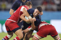 Scotland's Adam Hastings is tackled by Russia's Dmitry Gerasimov, left, and Vitaly Zhivatov during the Rugby World Cup Pool A game at Shizuoka Stadium Ecopa between Scotland and Russia in Shizuoka, Japan, Wednesday, Oct. 9, 2019. (AP Photo/Christophe Ena)