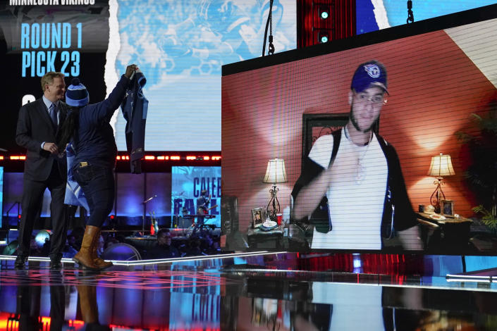 An image of Virginia Tech defensive back Caleb Farley is displayed as a Tennessee Titans fan cheers on stage after Farley was chosen by the Titans with the 22nd pick in the first round of the NFL football draft Thursday April 29, 2021, in Cleveland. (AP Photo/Tony Dejak)