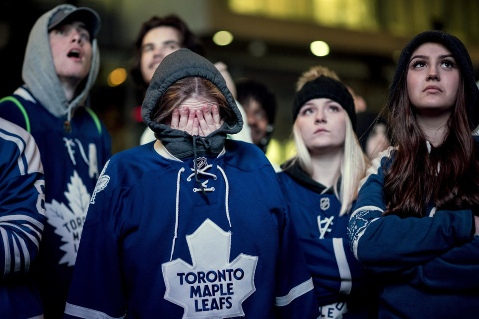 Fans react in Toronto on Tuesday, April 23, 2019, as the Toronto Maple Leafs lose to the Boston Bruins and are eliminated from the Stanley Cup NHL hockey playoffs. Fans watched the action from Boston on large outdoor screens in Maple Leaf Square in Toronto. (Christopher Katsarov/The Canadian Press via AP)
