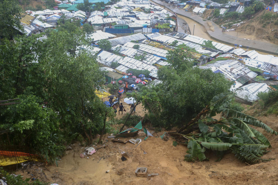 Rohingya refugees and others hold umbrellas as they search for survivors after a landslide triggered by heavy rains in a camp at Ukhiya in Cox's Bazar district, Bangladesh, Tuesday, July 27, 2021. (AP Photo/ Shafiqur Rahman)