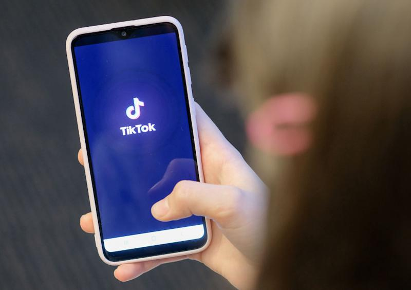 A girl is holding her smartphone with the logo of the short video app TikTok in her hands.
