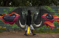 A woman wearing a face mask as a precaution against coronavirus outbreak, walks on the street in downtown Johannesburg, South Africa, Tuesday, Jan. 26, 2021. (AP Photo/Themba Hadebe)