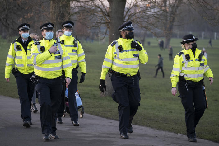 A day after London Mayor Sadiq Khan announced the spread of Covid is said to be out of control, Met police officers walk towards a group of Covid-deniers who are challenging lockdown rules and authoritarian control at passing south Londoners in Brockwell Park in Lambeth and during the third pandemic lockdown, on 9th January 2021, in London, England. The Coronavirus infection rate in London has exceeded 1,000 per 100,000 people, based on the latest figures from Public Health England although the Office for National Statistics recently estimated as many as one in 30 Londoners has coronavirus. (Photo by Richard Baker / In Pictures via Getty Images)