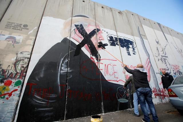 <p>A Palestinian man crosses out a mural depicting U.S. President Donald Trump that is painted on a part of the Israeli barrier, in the West Bank city of Bethlehem Dec. 7, 2017. (Photo: Mussa Qawasma/Reuters) </p>