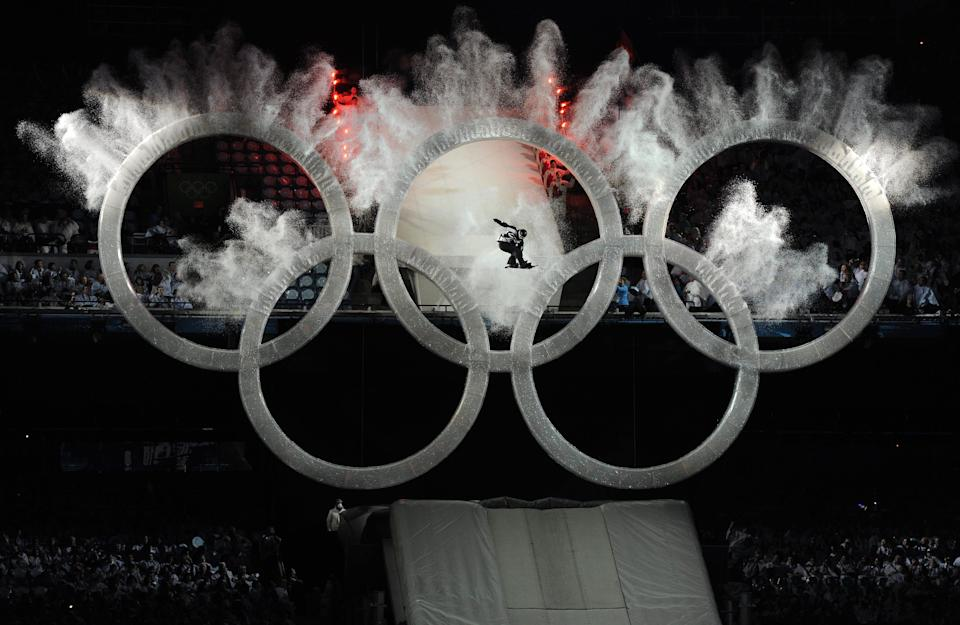 A snowboarder flies through the center ring of the Olympic Rings, triggering an explosion of snow and ice off the rings at BC Place during the opening ceremony of the 2010 Winter Olympics in Vancouver on February 12, 2010.