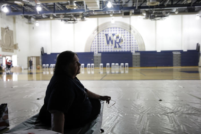 Mary Lewis, an evacuee from the Tick Fire, sits on a cot at a shelter inside the West Ranch High School gym Friday, Oct. 25, 2019, in Santa Clarita, Calif. (AP Photo/Marcio Jose Sanchez)