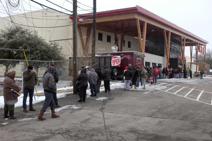 People stand in line outside an HEB grocery store in the snow Thursday, Feb. 18, 2021, in Austin, Texas. The store did not have milk, eggs, meat or refrigerated items. Temperatures dropped into the single digits as snow shut down air travel and grocery stores.(AP Photo/Ashley Landis)