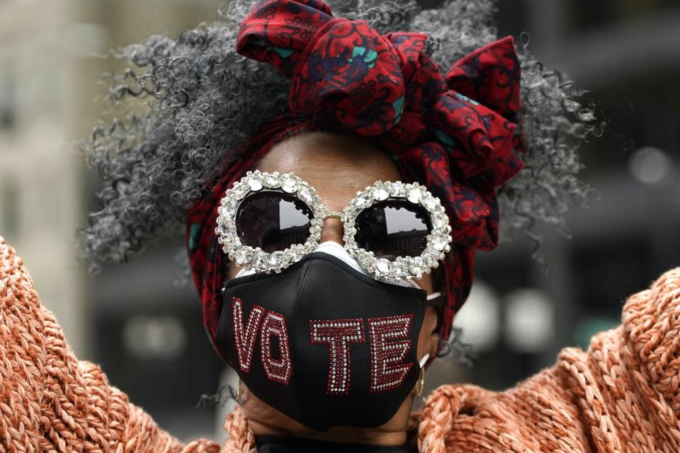 A Black woman wears a face mask embroidered with the word vote.