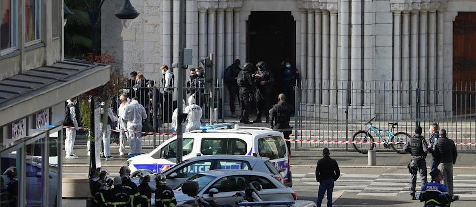 French members of the elite tactical police unit RAID enter to search the Basilica of Notre-Dame de Nice after a knife attack in Nice on October 29, 2020. - A man wielding a knife outside a church in the southern French city of Nice slit the throat of one person, leaving another dead and injured several others in an attack on Thursday morning, officials said. The suspected assailant was detained shortly afterwards, a police source said, while interior minister Gerald Darmanin said on Twitter that he had called a crisis meeting after the attack. (Photo by Valery HACHE / AFP)