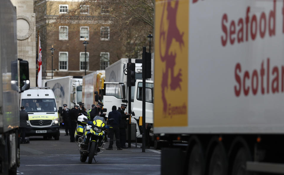 Police speak to shellfish export truck drivers as they are stopped for an unnecessary journey in London, Monday, Jan. 18, 2021, during a demonstration by British Shellfish exporters to protest Brexit-related red tape they claim is suffocating their business. The drivers were later stopped by police and issued with fines for an 'unnecessary journey' due to the national lockdown to curb the spread of the coronavirus. (AP Photo/Alastair Grant)