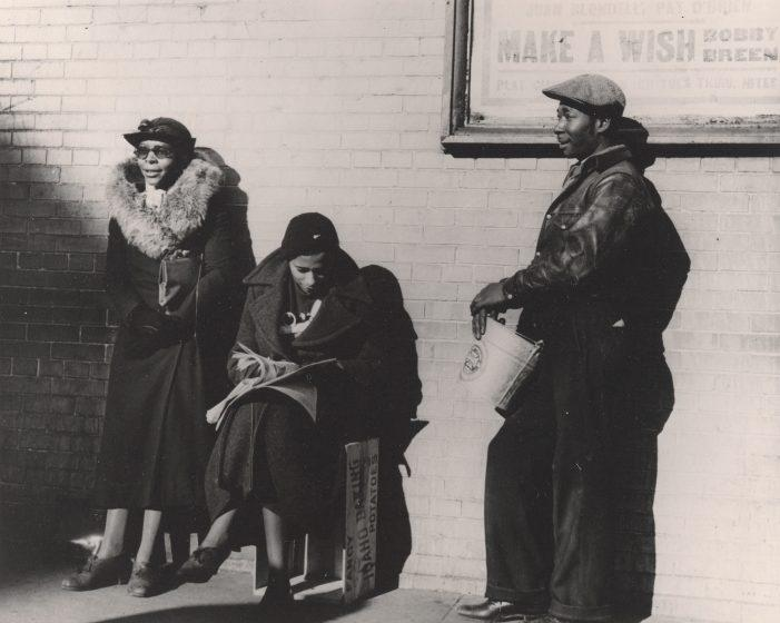 A vintage black and white image show two Black women and one Black man in the sunshine before a brick wall