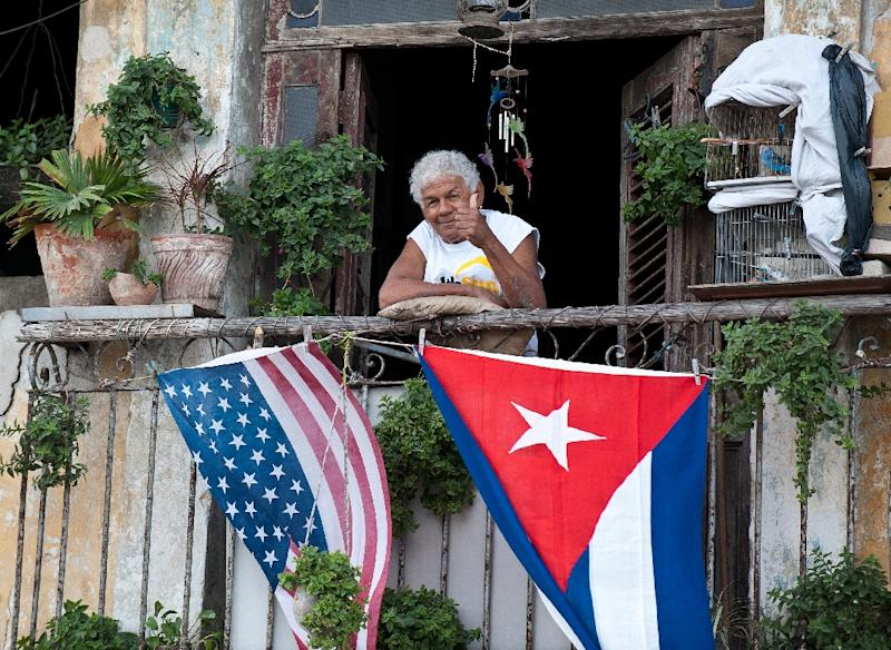 A Cuban gives the thumbs up from his balcony decorated with the US and Cuban flags in Havana, on January 16, 2015 (AFP Photo/Yamil Lage)