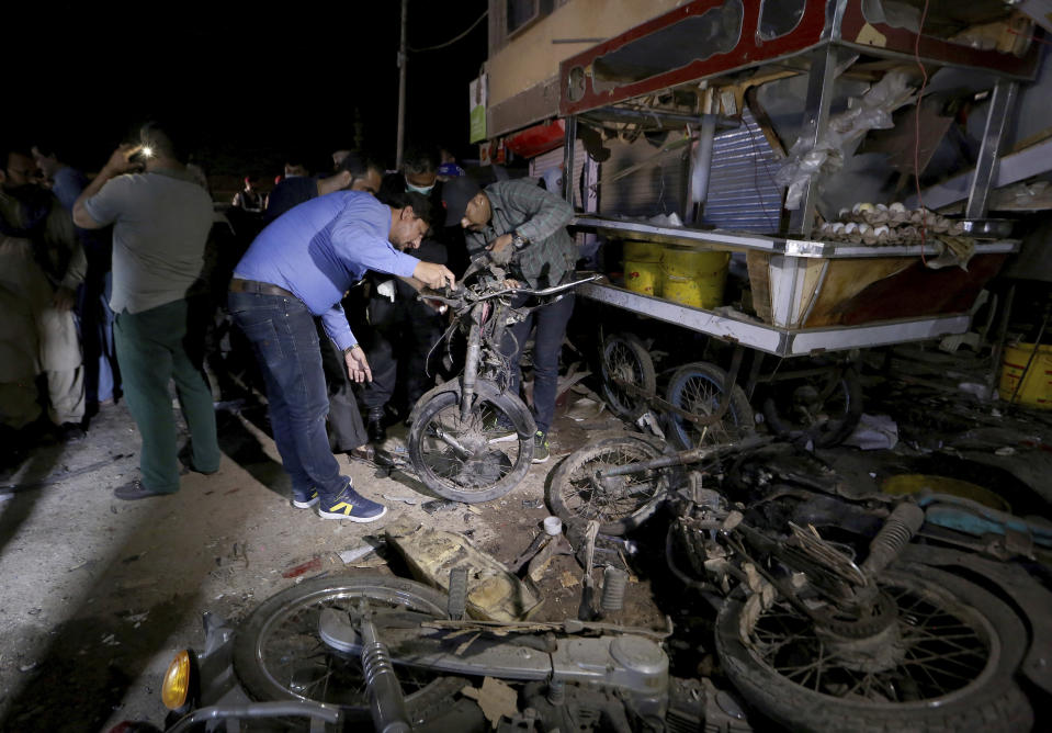 Pakistani security officials examine the site of explosion, in Karachi, Pakistan, Monday, March 15, 2021. The roadside bomb went off near a vehicle carrying paramilitary rangers in southern Pakistan on Monday, killing and wounding some people, mostly pedestrians, authorities said. (AP Photo/Fareed Khan)