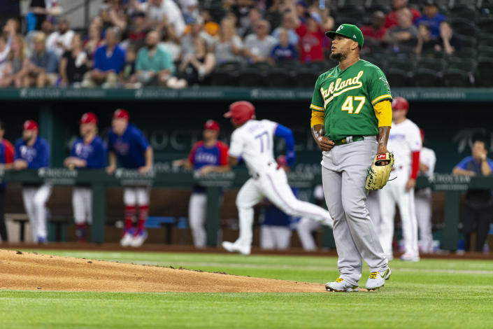 Oakland Athletics starting pitcher Frankie Montas (47) watches as Texas Rangers' Andy Ibáñez's (77) home run flies during the first inning of a baseball game, Monday, June 21, 2021, in Arlington, Texas. (AP Photo/Sam Hodde)
