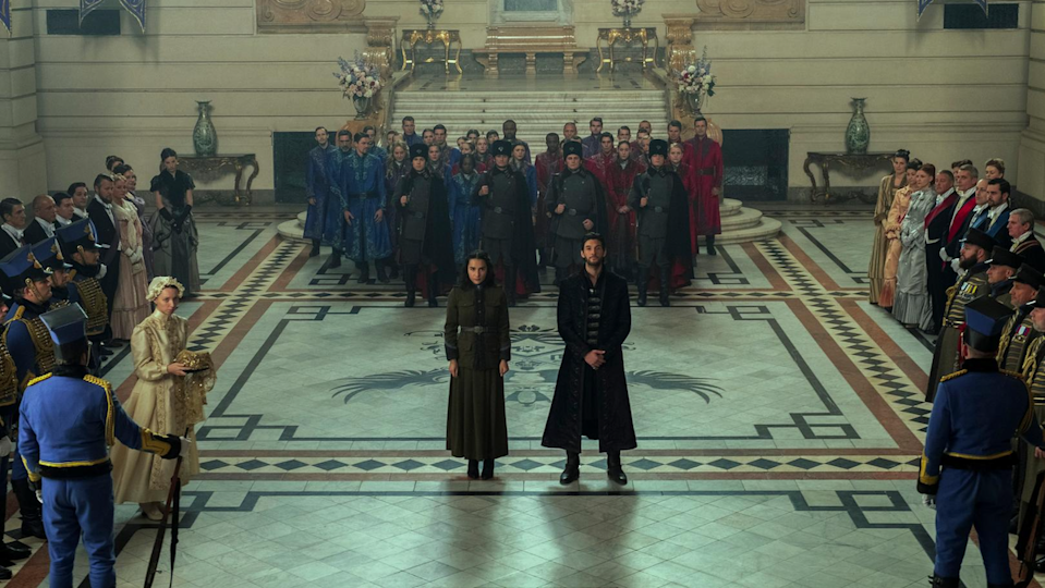 Alina and General Kirigan stand in front of the Grisha in the Little Palace in Shadow and Bone