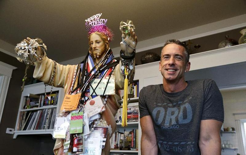 """In this photo taken on May 22, 2013, author Dan Savage stands with a three-foot tall statue of Jesus, adorned with old press credentials, rosaries, beads and other miscellaneous items, in his home in Seattle. Savage's latest book, """"American Savage,"""" was released on Tuesday, May 28. (AP Photo/Elaine Thompson)"""