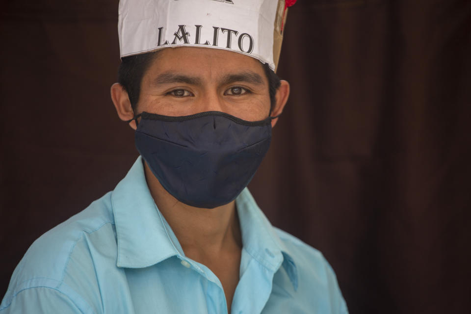 """Teacher Gerardo Ixcoy, wearing a protective face mask, found a way to give individual instruction to his sixth-grade students amid the new coronavirus pandemic, in Santa Cruz del Quiche, Guatemala, Wednesday, July 15, 2020. Ixcoy, known universally as """"Lalito 10"""", quickly realized there were challenges to remote learning in this farming community in Guatemala's western highlands and invested his savings in an adult tricycle and converted it into a mobile classroom. (AP Photo/Moises Castillo)"""
