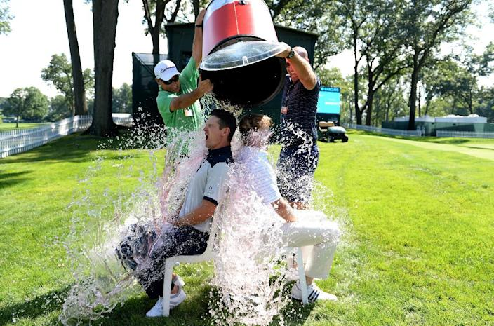 Justin Rose of England and Brandt Snedeker of the USA take the 'ice bucket challenge' with a bit of help from their caddies after a practice round prior to The Barclays on August 19, 2014 in Paramus, New Jersey (AFP Photo/Ross Kinnaird)