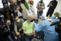 """Germany's tourist Uwe Keim, center, wearing a face mask to protect against coronavirus gets the first shot of Russia's Sputnik V coronavirus vaccine in Moscow, Russia, Friday, April 16, 2021. Uwe Keim, 46-year-old software developer from Stuttgart, told The Associated Press after getting his jab that he isn't worried about depriving some Russian of their shot, as he believes """"there are more vaccines available here in Russia than is demanded by the people here."""" (AP Photo/Pavel Golovkin)"""