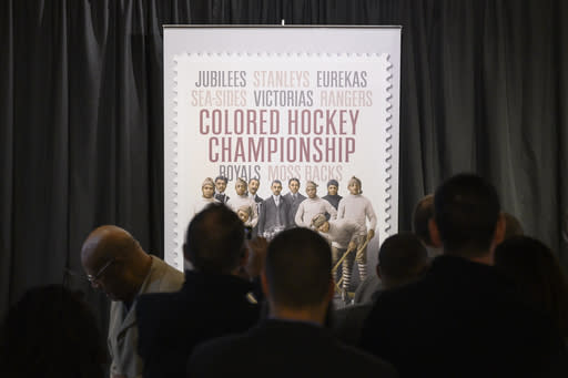 People gather to photograph Canada Post's newly unveiled stamp honouring the Colored Hockey Championship and the all-Black hockey teams in the Maritimes between 1895 and the early 1930s during an event at the Black Cultural Center in Halifax, Nova Scotia, Thursday, Jan. 23, 2020. (Darren Calabrese/The Canadian Press via AP)
