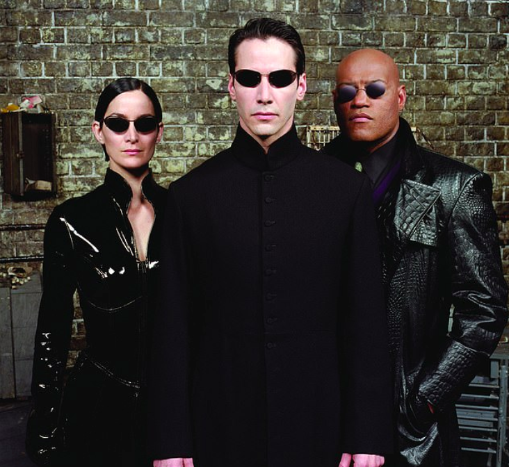 "Carrie Ann Moss, Keanu Reeves e Laurence Fishburne in una scena di ""Matrix"", 1999 (Warner Bros)."
