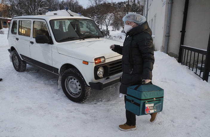 A medical worker carries a thermal bag with vaccines from a clinic in Lakhdenpokhya to drive to Ikhala, one of several remote villages in the village of Ikhala in Russia's Karelia region, Tuesday, Feb. 16, 2021. Russia's rollout of its coronavirus vaccine is only now picking up speed in some of its more remote regions, although experts say the campaign is still moving slowly. (AP Photo/Dmitri Lovetsky)