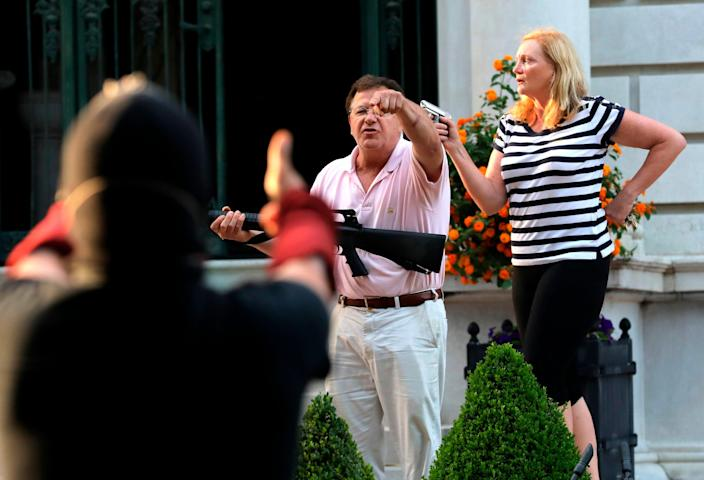 Armed homeowners Mark and Patricia McCloskey confront Black Lives Matter protesters in St Louis on 28 June, 2020 (AP)