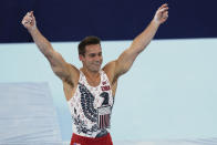 FILE - In this July 24, 2021, file photo, Samuel Mikulak, of the United States, celebrates his performance on the parallel bars during the men's artistic gymnastic qualifications at the 2020 Summer Olympics in Tokyo. In arenas across Tokyo, athletes accustomed to feeding off the deafening roar of the crowd are searching for new ways to feel Olympic enthusiasm. (AP Photo/Natacha Pisarenko, File)