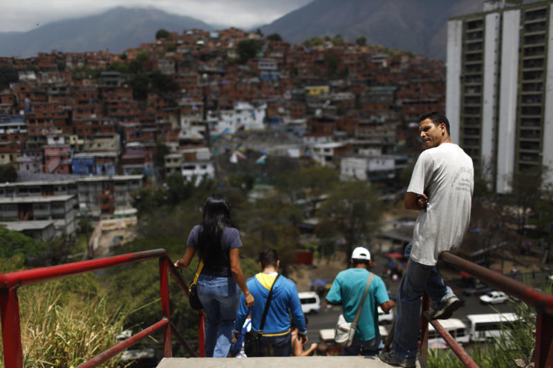 In this March 14, 2013 photo, a man sits on the railing of a walkway in a shantytown in Caracas, Venezuela. In 2011, the city suffered a homicide rate of an astounding 99 killed out of every 100,000 people, making it the sixth deadliest city in the world, according to the Mexican public safety group Security, Justice and Peace. (AP Photo/Rodrigo Abd)
