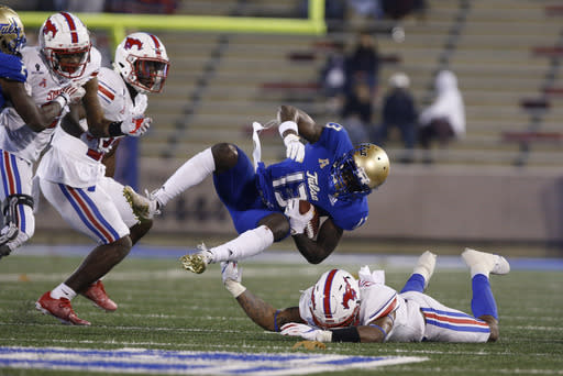 Tulsa wide receiver Josh Johnson (13) is knocked off his feet by a SMU defender after a catch during the second half of an NCAA college football game in Tulsa, Okla., Saturday, Nov. 14, 2020. (AP Photo/Joey Johnson)