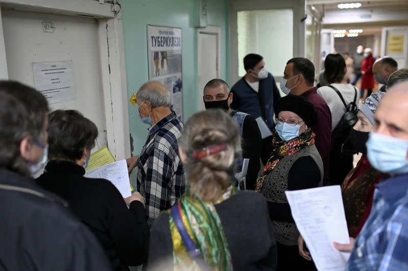 People wearing protective face masks wait in a queue at a clinic in Omsk