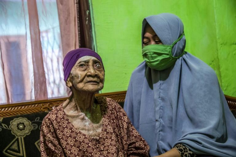 Kamtim, 100, sits in her living room with her daughter-in-law Siti Aminah in Surabaya, East Java after recovering from coronavirus