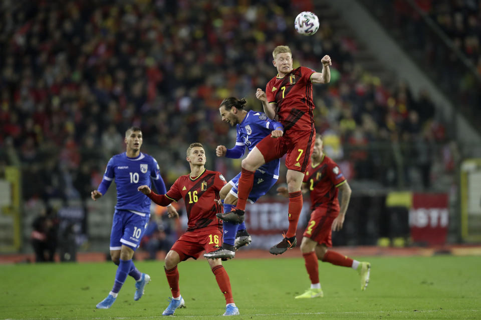 Belgium's Kevin De Bruyne, right, jumps for the ball with Cyprus' Christos Wheeler during the Euro 2020 group I qualifying soccer match between Belgium and Cyprus at the King Baudouin stadium in Brussels, Tuesday, Nov. 19, 2019. (AP Photo/Francisco Seco)