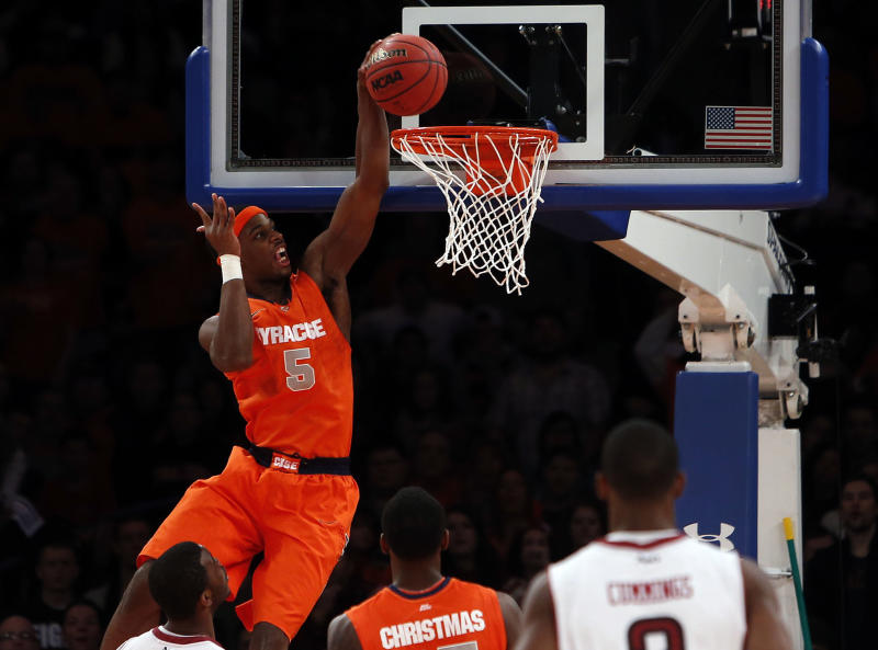 Syracuse's C.J. Fair (5) dunks against Temple during the first half of an NCAA college basketball game in the Gotham Classic at Madison Square Garden, Saturday, Dec. 22, 2012, in New York. (AP Photo/Jason Decrow)