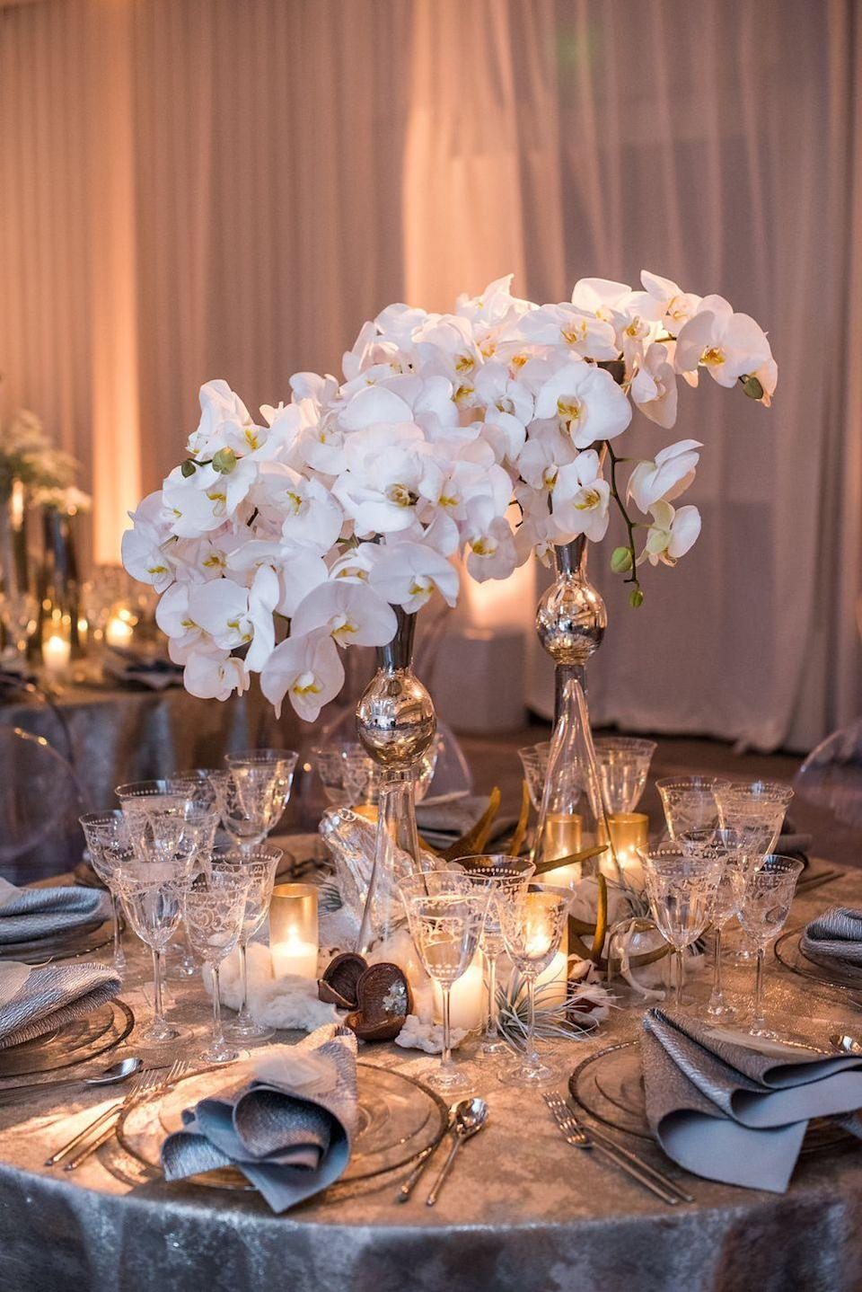 "<p>If you're worried about matching your centerpiece with the rest of your colorful Christmas decor, remember that white flowers are typically a safe bet for the holidays. Here, towering blooms are illuminated by clusters of glowing candles. </p><p><em>Via </em><a href=""http://www.kristinbanta.com/"" rel=""nofollow noopener"" target=""_blank"" data-ylk=""slk:Kristin Banta Events"" class=""link rapid-noclick-resp""><em>Kristin Banta Events</em></a></p>"
