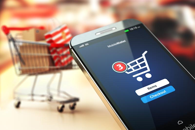 A smartphone displaying a mobile commerce app with a shopping cart in the background