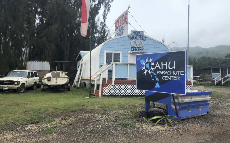"FILE - This June 28, 2019 file photo, shows the Oahu Parachute Center near Dillingham Airfield in Waialua, Hawaii. The skydiving company that was operating a plane that crashed and killed 11 people last month did not have the proper state permits to take people skydiving. Documents released by the state Wednesday, July 10, 2019, show Oahu Parachute Center was ""not in good standing"" with the Department of Commerce and Consumer Affairs as of April 2019. It also was not a registered tenant for the state land it occupied. (AP Photo/Caleb Jones, File)"