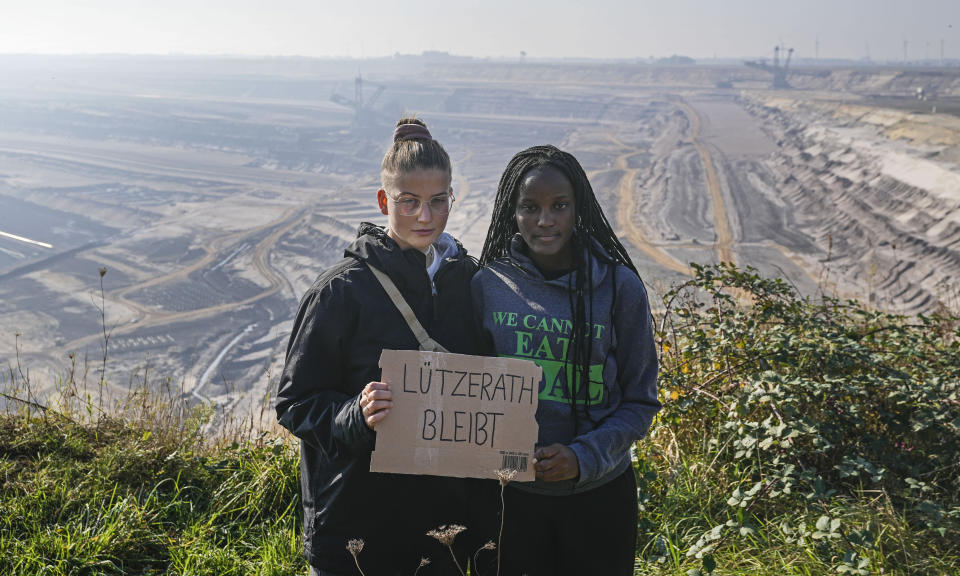 """Climate activists Vanessa Nakate from Uganda, right, and Leonie Bremer of the German Fridays for Future movement, hold a sign that reads: """"Luetzerath stays"""" during their visit to the Garzweiler open-cast coal mine in Luetzerath, western Germany, Saturday, Oct. 9, 2021. The village of Luetzerath, now almost entirely abandoned as the mine draws ever closer, will be the latest village to disappear as coal mining at the Garzweiler mine expands. Garzweiler, operated by utility giant RWE, has become a focus of protests by people who want Germany to stop extracting and burning coal as soon as possible. (AP Photo/Martin Meissner)"""