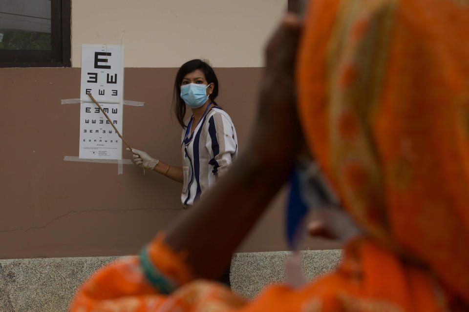 """A patient gets her eye checked during her follow up after her cataract surgery at an eye camp in Lumbini, 288 kilometers (180 miles) south west of Kathmandu, Nepal, March 31, 2021. Nepal's """"God of Sight"""" eye doctor renowned for his innovative and inexpensive cataract surgery for the poor is taking his work beyond the Himalayan mountains to other parts of the world so there is no more unnecessary blindness in the world. Ruit, who has won many awards for his work and performed some 130,000 cataract surgery in the past three decades, is aiming to expand his work beyond the borders of his home country and the region to go globally. (AP Photo/Bikram Rai)"""